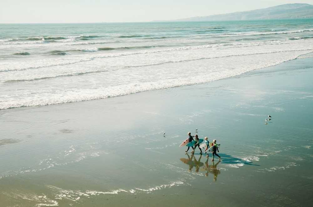 Four surfers at a learn to surf destination in Europe