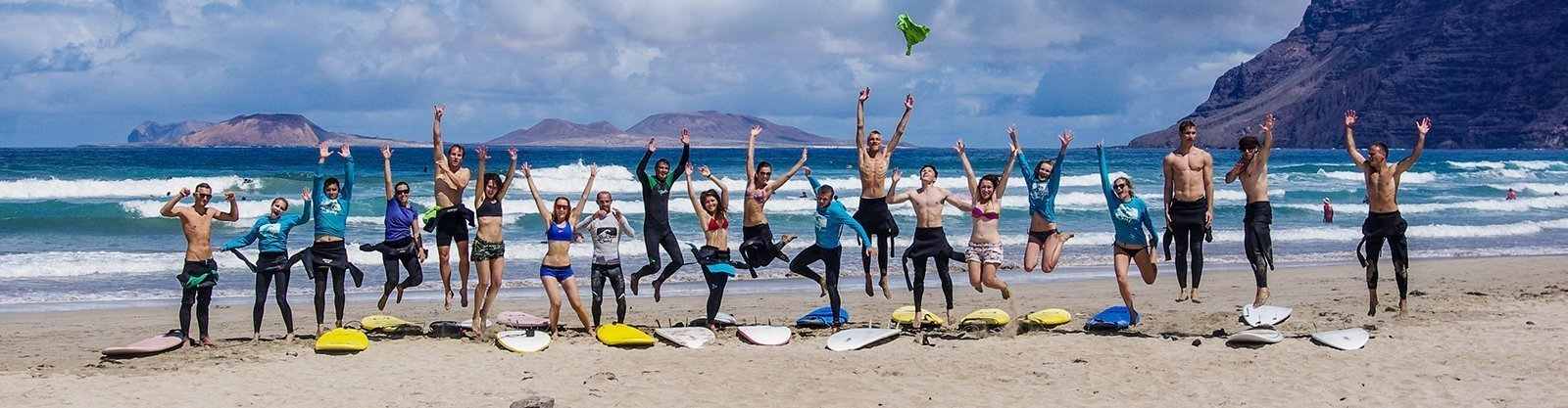 group surfing lessons with surf school and surf camp on the beach playa famara lanzarote redstarsurf accommodation and surf lessons escuela de surf in canary islands surf camp ecole de surf серф школа серф-кемп серф-лагерь