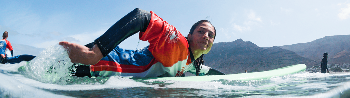 girl taking surfing lessons in famara lanzarote with redstarsurf paddling out