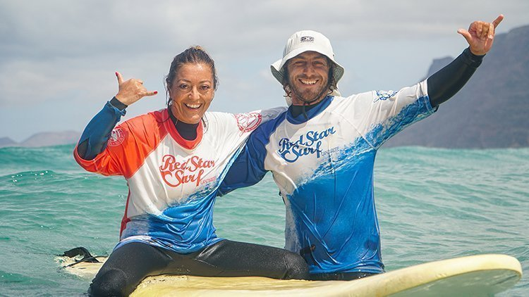happy surfer with surf instructor surf school and surf camp on the beach playa famara lanzarote with redstarsurf accommodation and surf lessons escuela de surf in canary islands surf camp ecole de surf серф школа серф-кемп серф-лагерь
